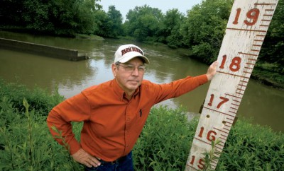 Warsaw, Illinois, farmer and chairman of the local drainage district, Sam Zumwalt, age 64, with the flood gage at the Hunt Drainage District pumping station. He has long been a champion of better flood control for the 16,000 acres of lowlands that make up the district. Water from the nearby Mississippi River reached 25-feet above flood stage in both 1993 and 2008. In the background is the outlet from the pumping station that can pump 200,000 gallons of water per minute off of the nearby farmland through a series of ditches and canals.