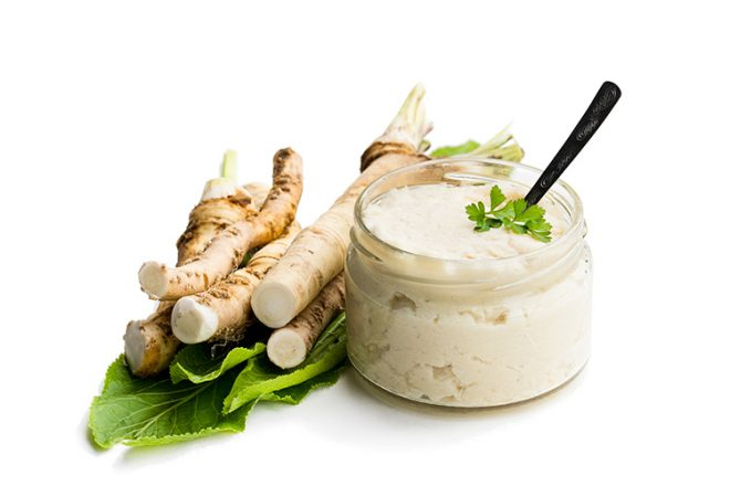Spicy horseradish sauce in glass jar isolated on white