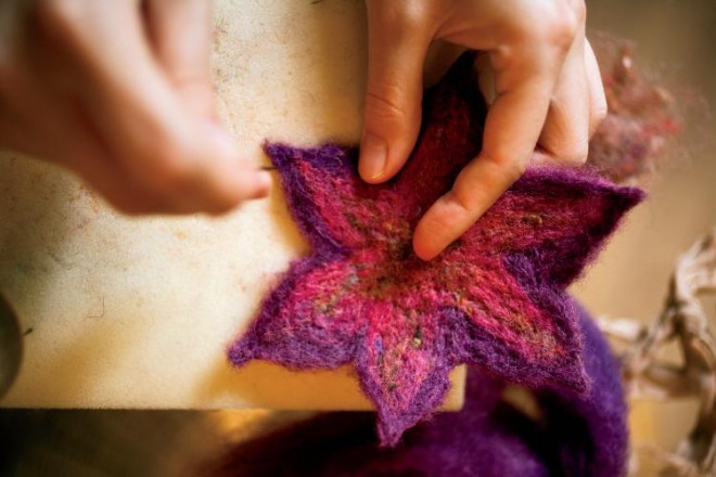 Natasha Lehrer, age 21, of Aurora, Illinois, uses a needle to stiffen and intertwine the fibers in a process known as felting to make a flower that will become a pin.  She founded Esther's Place Fiber Arts Studio when she was 19-years-old with the help of her parents.