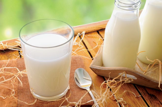 Glass of milk on a table on the field